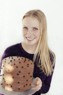 Portrait of smiling young woman holding cake stand with chocolate cake - MFF000894