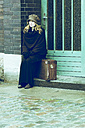 Woman sitting on her suitcase waiting - NG000107