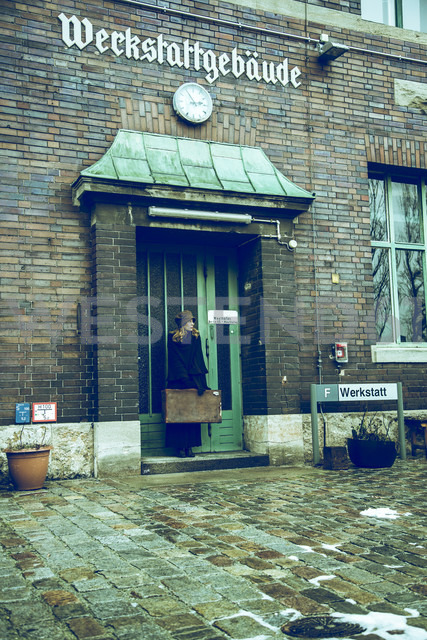 Germany, Berlin, woman with suitcase waiting at entrance of old industrial building - NG000122 - Nadine Ginzel/Westend61
