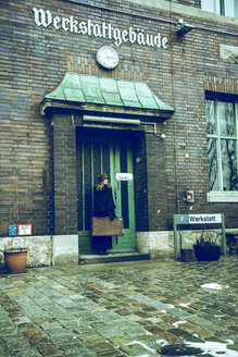 Germany, Berlin, woman with suitcase waiting at entrance of old industrial building - NG000122