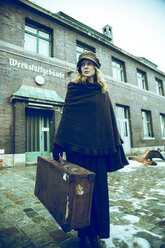 Germany, Berlin, woman carrying suitcase in front of old industrial building - NG000081