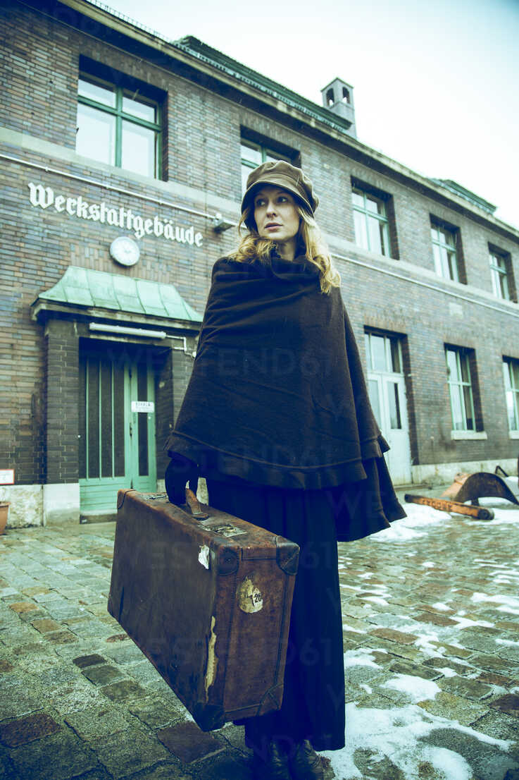 Germany, Berlin, woman carrying suitcase in front of old industrial building - NG000081 - Nadine Ginzel/Westend61