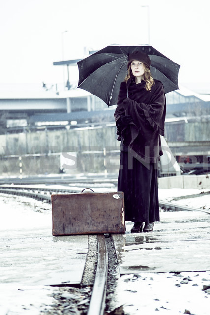Germany, Berlin, woman with umbrella and old suitcase waiting at platform in winter - NG000082 - Nadine Ginzel/Westend61