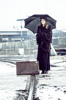 Germany, Berlin, woman with umbrella and old suitcase waiting at platform in winter - NG000082