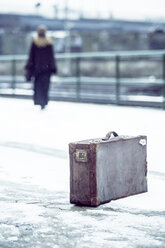 Germany, Berlin, woman with umbrella and old suitcase waiting at platform in winter - NG000086