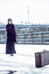 Germany, Berlin, woman with umbrella and old suitcase waiting at platform in winter - NG000087