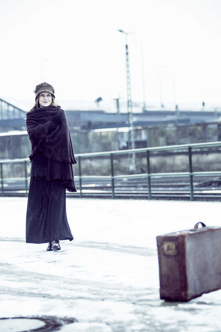 Germany, Berlin, woman with umbrella and old suitcase waiting at platform in winter - NG000087 - Nadine Ginzel/Westend61