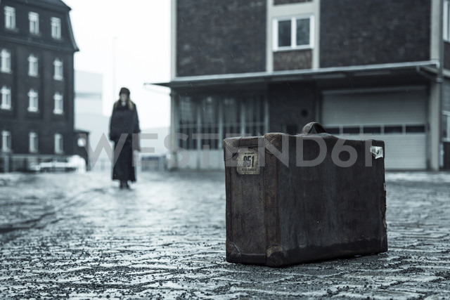 Woman standing on pavement in the background, old suitcase in front - NG000090 - Nadine Ginzel/Westend61