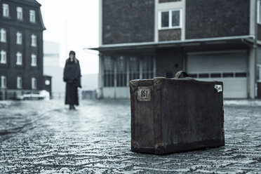 Woman standing on pavement in the background, old suitcase in front - NG000090