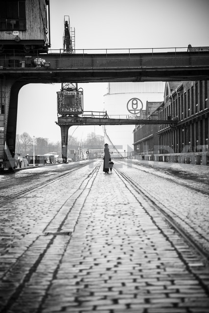 Germany, Berlin, woman with umbrella watching buildings at industrial harbour - NG000098 - Nadine Ginzel/Westend61