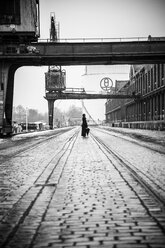Germany, Berlin, woman with umbrella watching buildings at industrial harbour - NG000098