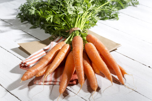 Bunch of organic carrots on cloth and white wooden table - MAEF007951