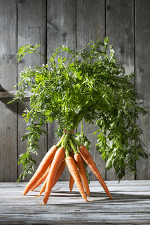 Bunch of organic carrots standing on grey wooden table in front of grey wooden wall - MAEF007954