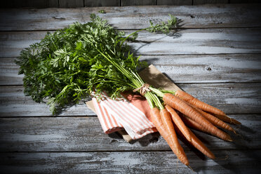 Bunch of organic carrots on cloth and grey wooden table - MAEF007955