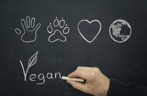 Man drawing vegan concept on blackboard, close-up - MW000014
