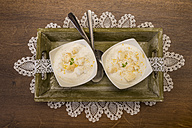 Two bowls of lemon curd creme with crumbled meringues on tablet and wooden table, elevated view - CSTF000034