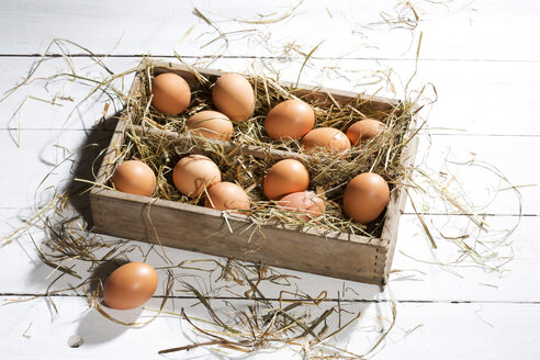 Wooden box of brown eggs and hay on white wooden table - MAEF007949