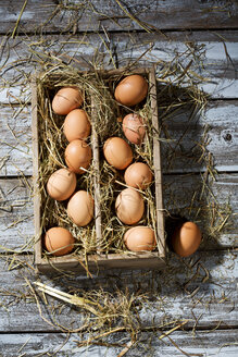 Wooden box of brown eggs and hay on grey wooden table - MAEF007941