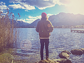 Austria, Mondsee, man standing at lake front - WV000457