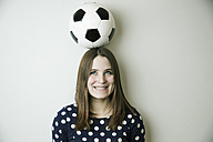 Portrait of smiling teenage girl with football on her head in front of white wall - JATF000670
