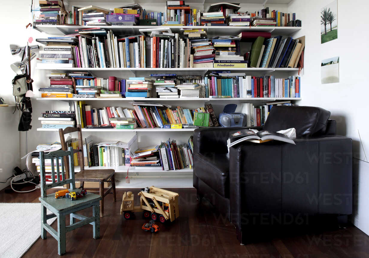 Book shelf and toys in a room with armchair and chairs - TKF000294 - TeKa/Westend61