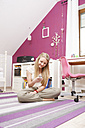 Happy teenage girl at her room using smartphone - VTF000110