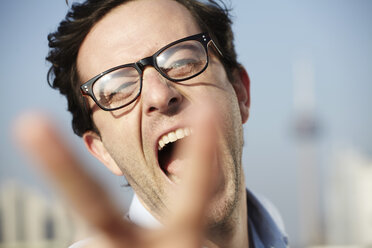 Portrait of screaming man showing victory sign - FMK000970
