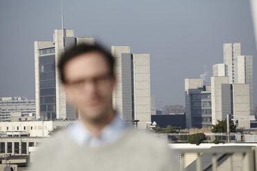 Defocused portrait of man in front of hifg-rise buildings - FMK000977