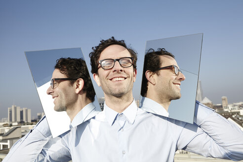 Portrait of smiling man holding two mirrors - FMK000983