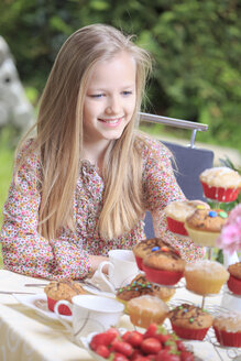 Portrait of smiling girl sitting at laid table - VTF000104
