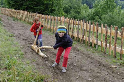 Germany, Bavaria, Celtic village Gabreta, Children pulling wooden plow - LB000574