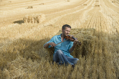 Man playing violin in stubble field - CRF002589