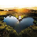 Austria, Salzburg State, Altenmarkt-Zauchensee, meditating woman at pond - HHF004733