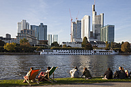 Germany, Hesse, Frankfurt, Financial district with River Main and people on riverbank - WI000433