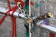 Germany, North Rhine-Westphalia, Muenster, chains with padlock on sprayed gate - WIF000425