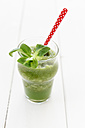 Glass of apple lamb's lettuce smoothie with spoon on white wooden table - EVGF000392