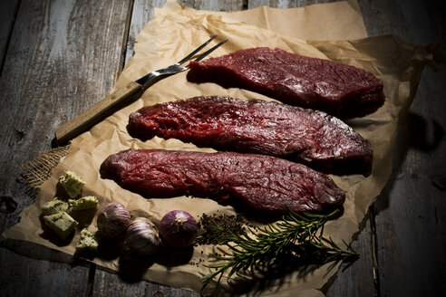 Beefsteak, garlic, rosemary, herb butter and pepper on baking paper - MAEF007984