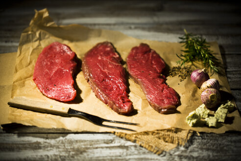 Beefsteak, garlic, rosemary, herb butter and pepper on baking paper - MAEF007983
