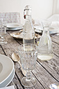 Glass, water bottle and carafe on festive laid table - LVF000749