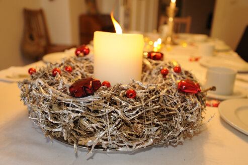 Advent wreath with lighted candle on laid table - LB000592