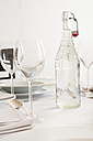 Festive laid table with wine glasses and bottle of water - LVF000767