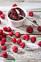 Bowl of raspberry jam, spoon and raspberries on wooden table - MAEF008001