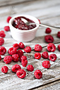 Bowl of raspberry jam, spoon and raspberries on wooden table - MAEF007999