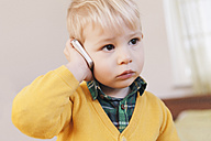 Portrait of serious looking toddler telephoning with smartphone - MFF000910