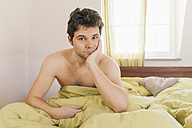 Portrait of shirtless man sitting in bed - MFF000909