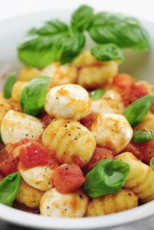 Bowl of gnocchi with tomato sauce, mozzarella balls and basil, close-up - IPF000066