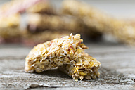 Two pieces of granola bar on wooden table, close-up - MAE008044