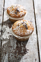 Two muffins in paper cups sprinkled with powdered sugar on wooden table - MAEF008046