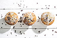 Row of three muffins in paper cups sprinkled with powdered sugar and chocolate shavings on white wooden table, elevated view - MAEF008061