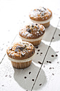 Row of three muffins in paper cups sprinkled with powdered sugar and chocolate shavings on white wooden table - MAEF008060